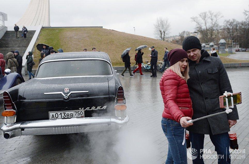 Жители Москвы фотографируются у автомобиля ГАЗ 13 Чайка перед стартом автопробега 108 минут в Москве, приуроченного к 56-й годовщине полета человека в космос