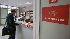 Посетитель у регистрационного стола в поликлинике. Архивное фото
