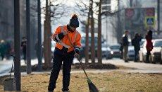 Работник коммунальных служб убирает улицу в Москве