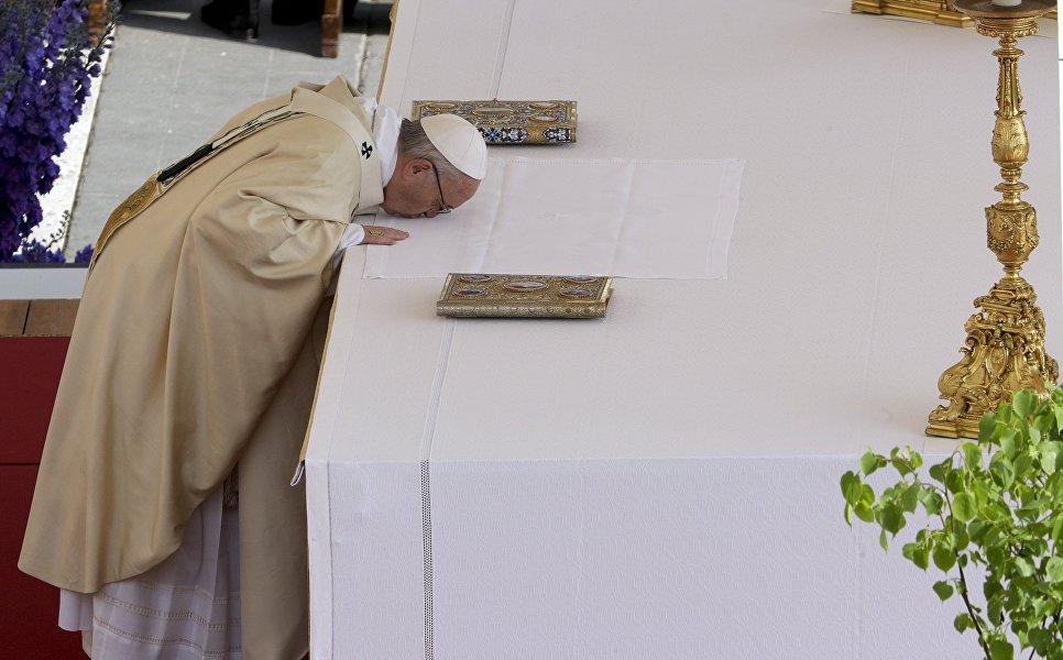 Папа римский Франциск целует алтарь, празднуя Пасху, на площади Святого Петра в Ватикане