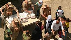 Раздача российской гуманитарной помощи офицерами Центра по примирению враждующих сторон в сирийской провинции. Архивное фото