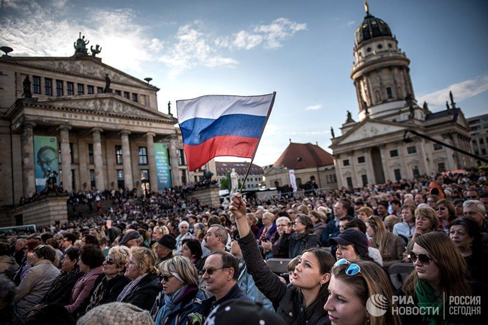 Посетители концерта Песни Победы солистов Хора Турецкого и женской арт-группы Soprano Турецкого на площади Жандарменмаркт в центре Берлина