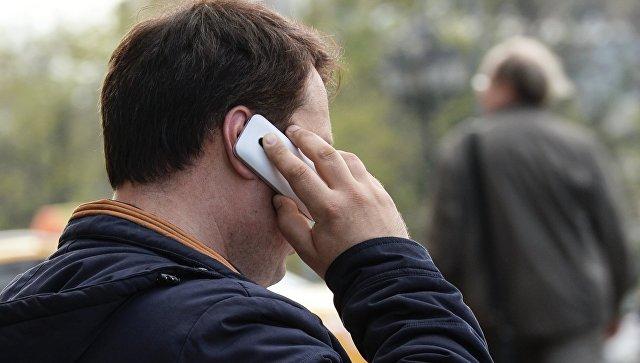 Мужчина говорит по телефону на улице Москвы. Архивное фото