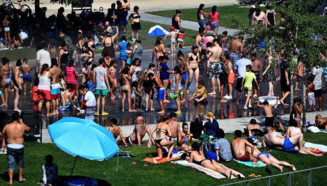 Жители Мадрида отдыхают на берегу реки Мансанарес во время жары, Испания. Архивное фото