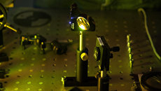 Линза голографической камеры, созданной российскими физиками, и лазерная искра (слева)