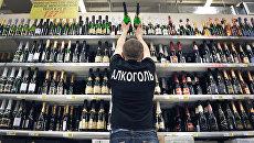 Продавец расставляет на полках бутылки шампанского вина. Архивное фото