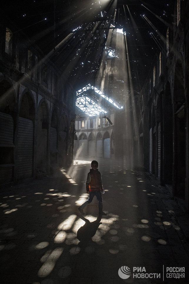 Дети играют в одном из зданий разрушенного района Хомса аль Хамидия.  Сирия,  12.12.2015