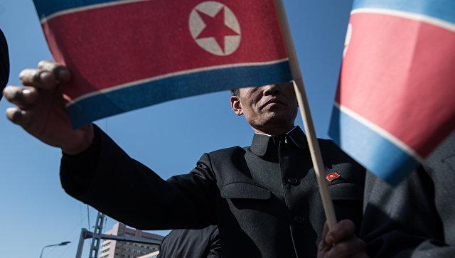 Мужчина с флагом КНДР в Пхеньяне. Архивное фото