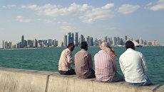 Мужчины сидят на набережной в Дохе, Катар. Архивное фото