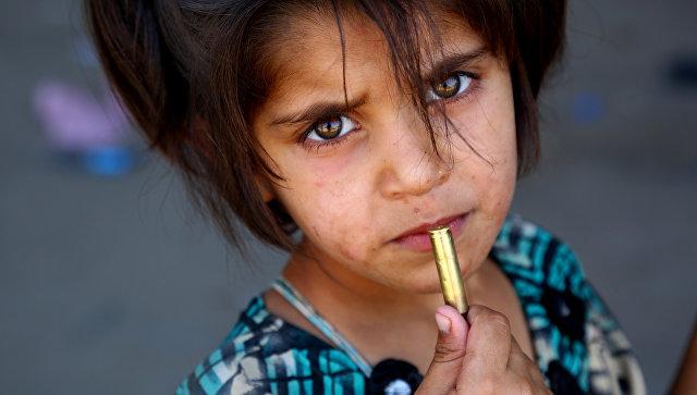 Сирийская девочка с патроном в руке в деревне Джазра в пригороде Ракки. Архивное фото