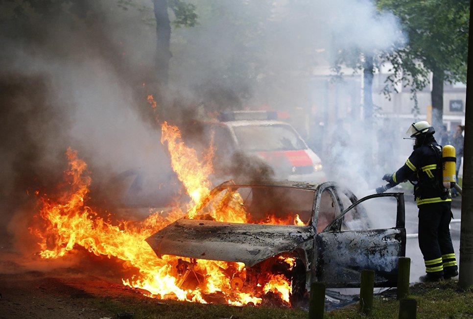 Тушение автомобиля после акций протестов против саммита G20 в Гамбурге
