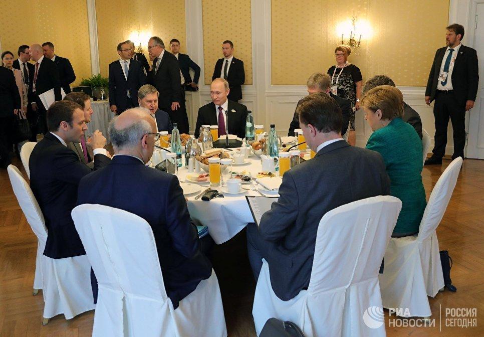 Президент РФ Владимир Путин во время совместного с канцлером Германии Ангелой Меркель и президентом Франции Эммануэлем Макроном завтрака на полях саммита лидеров Группы двадцати G20 в Гамбурге. 8 июля 201
