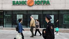 Прохожие у одного из филиалов банка Югра в Москве. Архивное фото