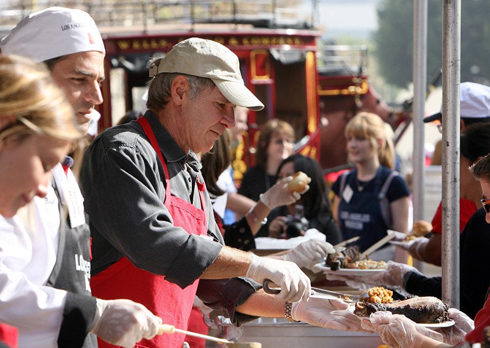 Американский актер Харрисон Форд во время раздачи еды бездомным накануне Дня Благодарения в США. 2001