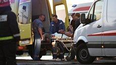 Сотрудники медицинской службы эвакуируют пострадавшего с места пожара в здании торгового центра РИО на Дмитровском шоссе