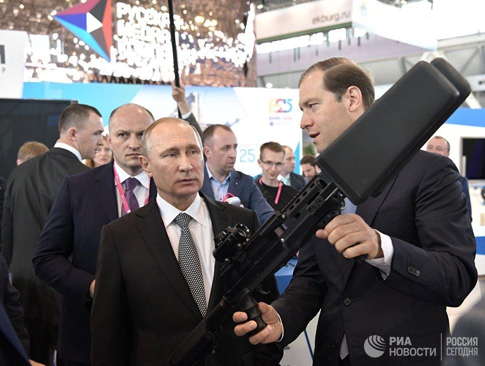 Владимир Путин знакомится с экспозицией стенда Минпромторга РФ на 8-й Международной промышленной выставке Иннопром - 2017