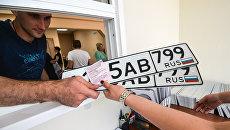 Выдача автовладельцу номерных знаков. Архивное фото