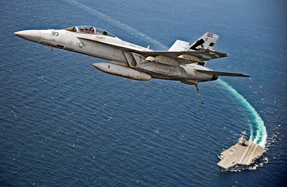 Самолет F/A-18F Super Hornet пролетает над авианосцем USS Gerald R. Ford в Атлантическом океане