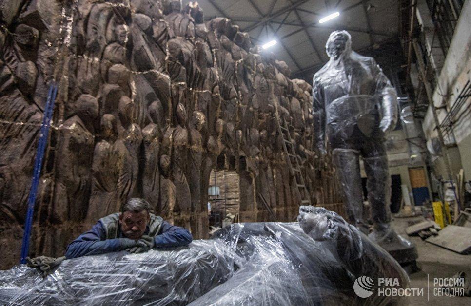 Рабочий возле монумента Стена скорби перед началом его транспортировки к месту установки в Москве