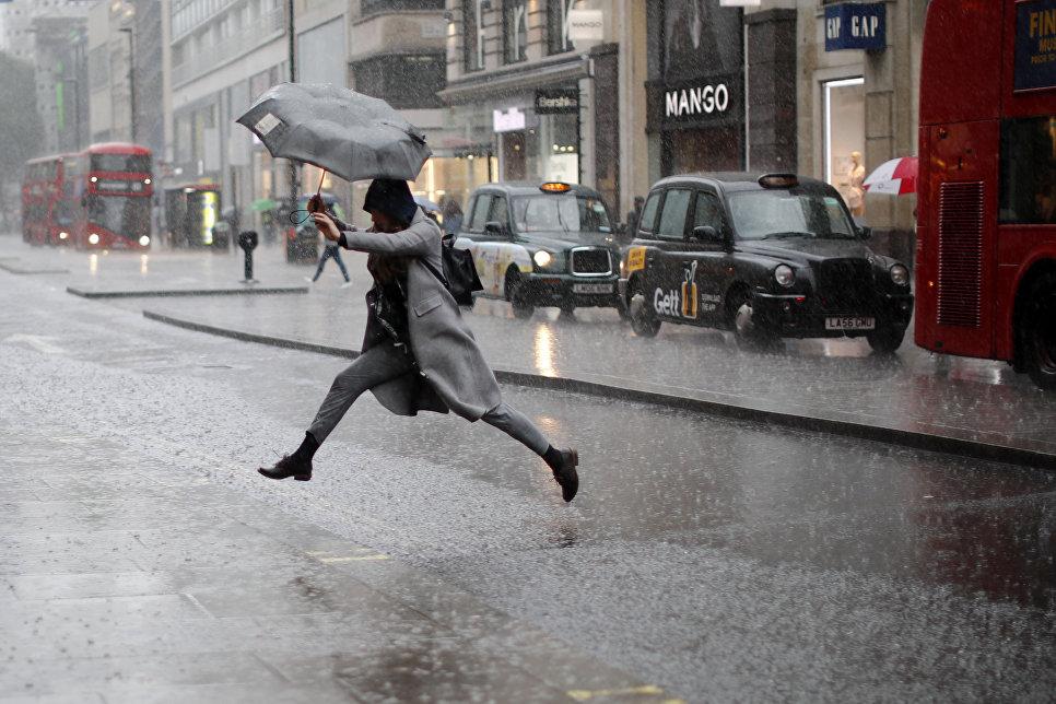 Девушка перепрыгивает лужу во время дождя в Лондоне. 9 августа 2017