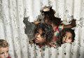 Палестинские дети смотрят на улицу через отверстие в заборе в Газе