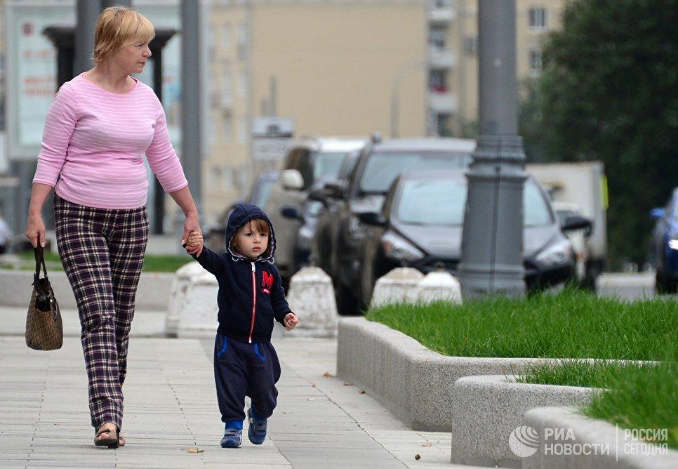 Женщина с ребенком идут по улице в Москве. Архивное фото
