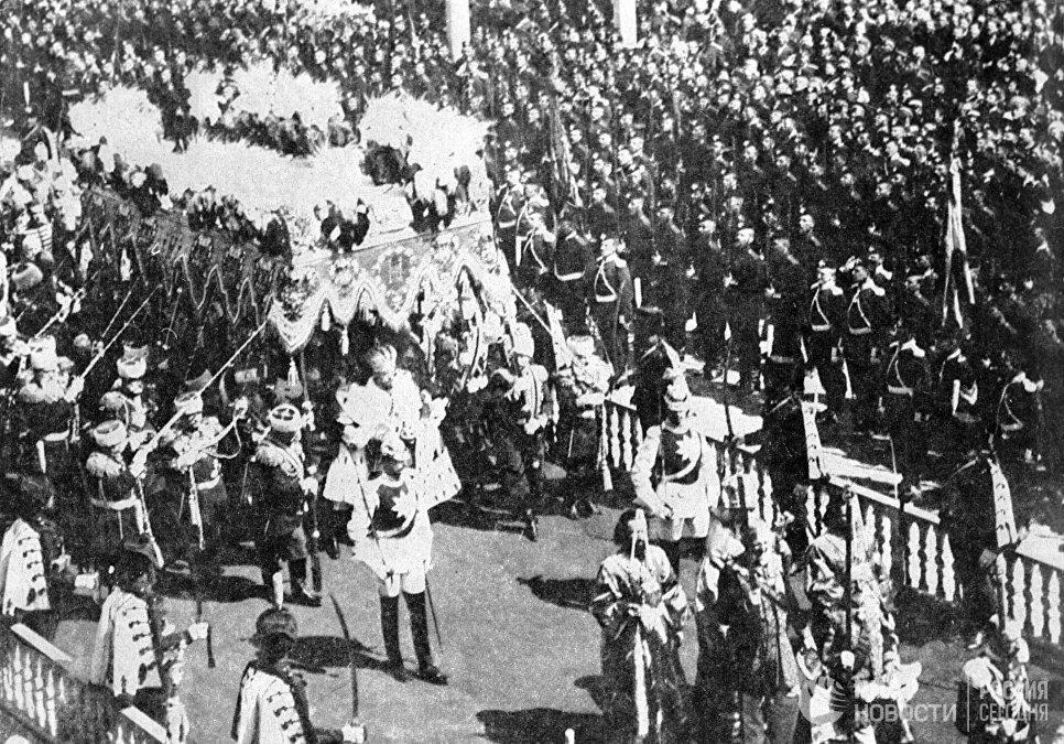 Николай II в царской мантии с короной, скипетром и жезлом шествует под балдахином в Кремле