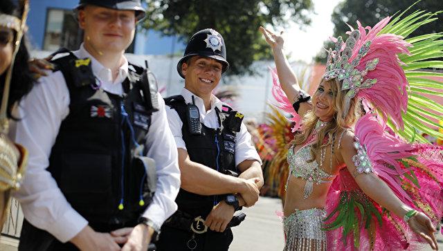 Участница ежегодного карнавал в лондонском районе Ноттинг-Хилл позирует с сотрудниками полиции