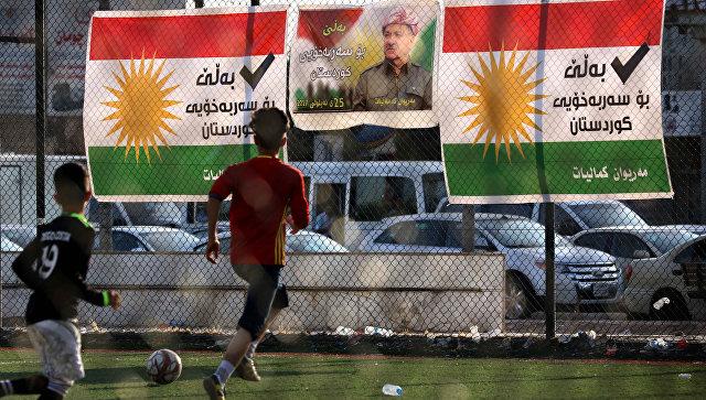Дети играют в футбол на фоне плаката с изображением лидера иракских курдов Масуда Барзани в поддержку независимости на предстоящем референдуме в Арбиле