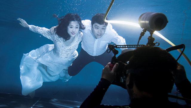 Молодожены фотографируются в подводной фотостудии в Пекине, Китай. 19 августа 2017