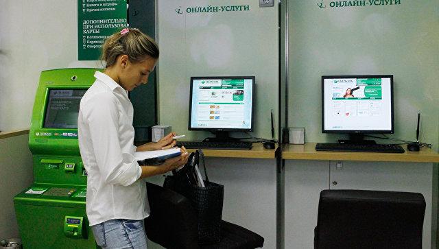 Сотрудница дополнительного офиса Сбербанка в зале обслуживания. Архивное фото