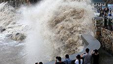 Люди на набережной в китайском Вэньлине во время тайфуна Тамлин. 14 сентября 2017