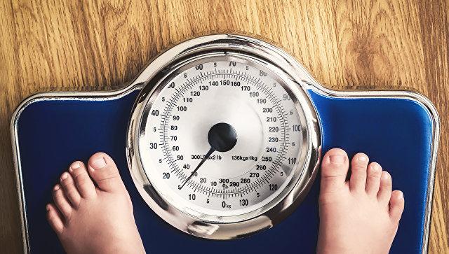 Ребенок взвешивается на весах