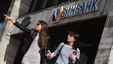 Девушки у одного из отделений Бинбанка в Москве