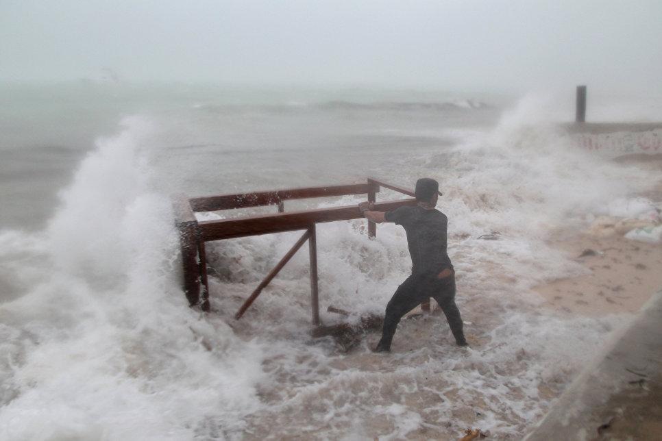 Мужчина пытается спасти стол, принадлежащий его ресторану до прибытия урагана Мария в Пунта-Кана, Доминиканская Республика. 20 сентября 2017 года