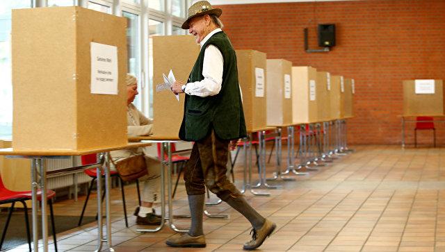 Мужчина в традиционной баварской одежде на избирательном участке в Мюнхене, Германия. 24 сентября 2017