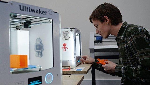 Юноша печатает на 3D принтере