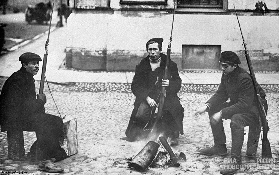 Красногвардейский патруль сидит у костра на улице Петрограда в первые дни Октябрьской революции