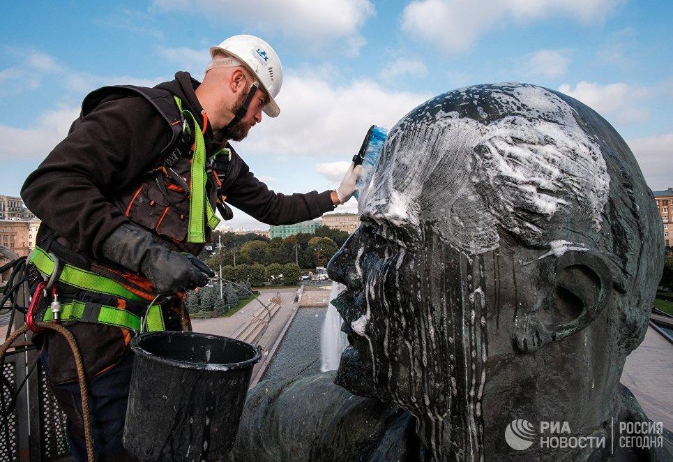 Сотрудник коммунальной службы моет памятник Ленину на Московской площади в Санкт-Петербурге.