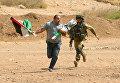 Израильский солдат бежит за палестинцем во время столкновений в городе Тубас на Западном берегу реки Иордан.