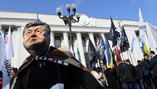 Участник акции протеста у здания Верховной рады в маске президента Украины Петра Порошенко