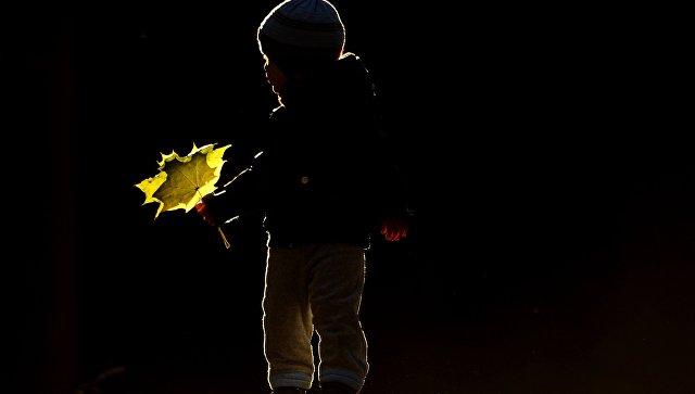 Ребенок играет с осенними листьями