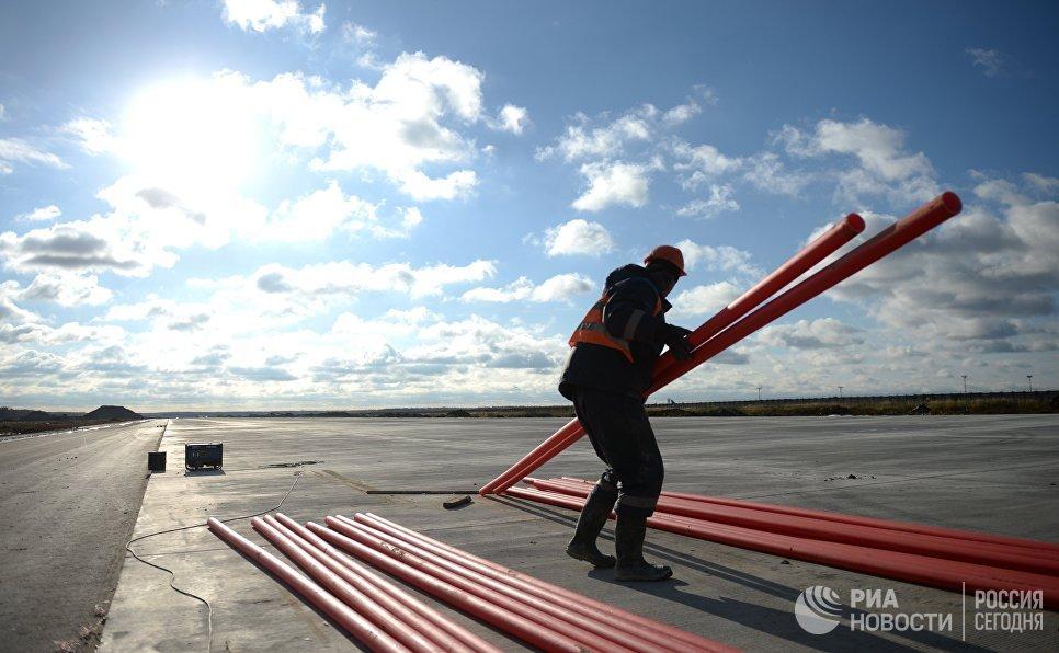 Рабочие на территории строительства взлетной полосы нового терминала аэропорта Домодедово