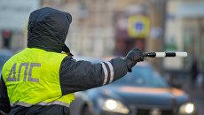 Сотрудник дорожно-патрульной службы дежурит на одной из улиц Москвы. Архивное фото
