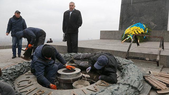 Рабочие удаляют цемент с оскверненного Вечного огня в Киеве. 7 ноября 2017