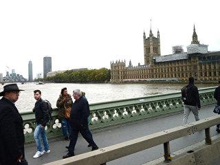 Прохожие на Вестминстерском мосту у Вестминстерского аббатства в Лондоне. Архивное фото