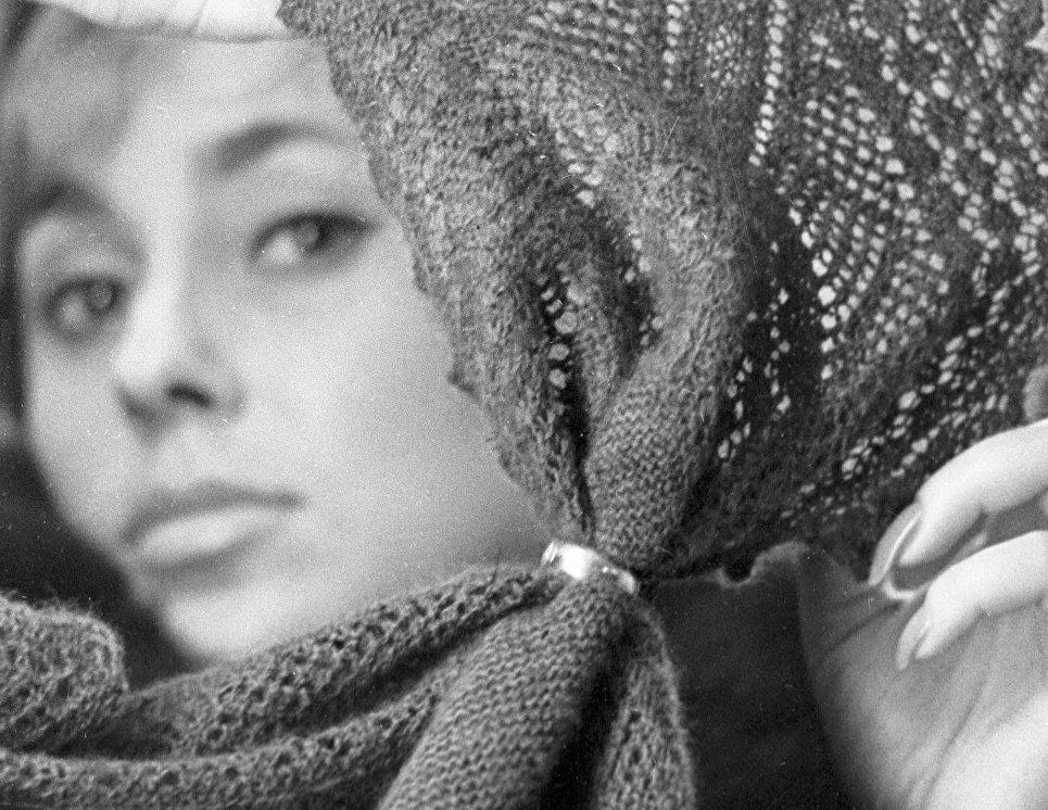 Девушка протягивает оренбургский пуховой платок сквозь золотое кольцо, демонстрируя его тонкость.