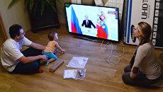 Молодая семья смотрит телевизионную трансляцию выступления президента РФ Владимира Путина
