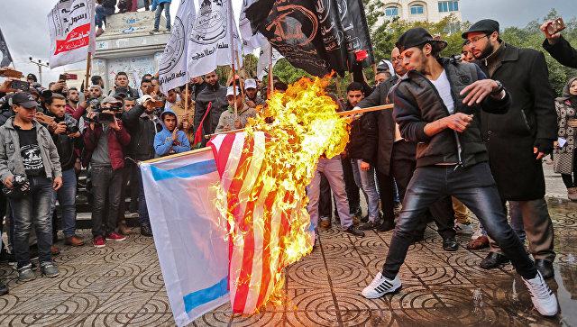 Палестинские протестующие сжигают американский и израильский флаги в городе Газа