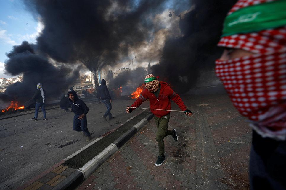 Палестинские протестующие во время столкновений с израильскими военными в районе города Рамалла на Западном берегу